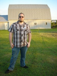 Zang standing in front of  a barn.